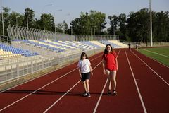 Little girl running on the stadium with a coach royalty free stock image