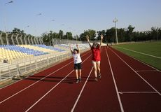 Little girl running on the stadium with a coach royalty free stock photo