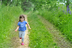 Little girl running in sunny blooming forest. Kids play outdoors. Summer fun for family with children. Little girl running through sunny blooming forest. Kids Royalty Free Stock Image