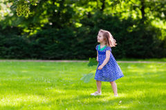 Little girl running in sunny park Stock Photos