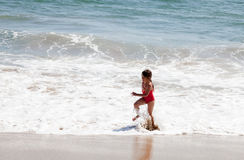 Little Girl Running in the Surf on the Beach Royalty Free Stock Photos