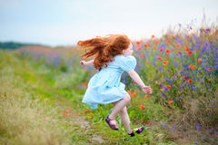 A little girl running to the field. Funny dynamic moment with jump. The a little girl running to the field. Funny dynamic moment with jump royalty free stock photography