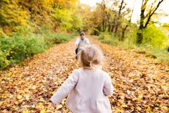 Little girl running to her father. Colorful autumn forest. Little girl running to the arms of her father. Family walk in colorful autumn forest Royalty Free Stock Photo