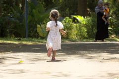Little girl running to her mom and brother on a dirt trail in a park Royalty Free Stock Image