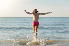 Little girl running to the sea, jump Stock Image