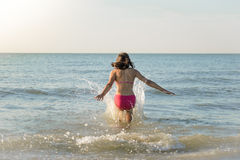 Little girl running to the sea, jump Royalty Free Stock Image