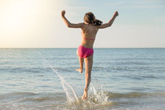 Little girl running to the sea, jump Stock Images