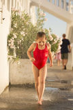 A little girl running under under flowing water Royalty Free Stock Images