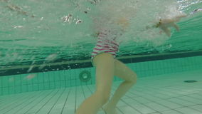 Little girl running underwater in swimming pool making bubbles stock footage