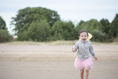Little girl running in waves against shore Royalty Free Stock Images