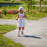 Little girl runs. On pavement royalty free stock photo
