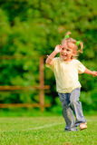 Little girl runs across field. Little girl with tails runs on green shelter and laughs Stock Images