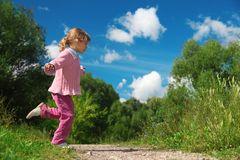 Little girl runs across path outdoor Stock Image