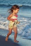 A little girl runs along the beach. Little smiling girl runs along the beach. Evening. Sunset Stock Image