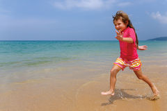 Little girl runs along the beach Stock Photo