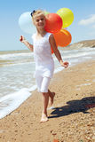 Little girl runs along the coastline with balloons Stock Image