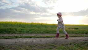 Little girl runs along field road, Running child, happy kid having fun outside city, healthy childhood, clean stock footage