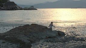 Little Girl Runs along Wet Sand Beach at Low Tide at Sunset stock video