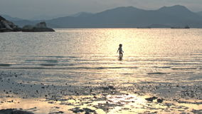 Little Girl Runs along Wet Sand Beach at Low Tide at Sunset stock video footage