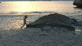 Little Girl Runs along Wet Sand Beach at Low Tide at Sunset stock footage