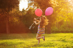 Little girl runs with balloons. Little girl with balloons running on the lawn in the park outdoors. Freedom and carefree. Happy childhood. Man is unrecognizable Stock Photography