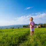 Little girl runs through a beautiful meadow royalty free stock image