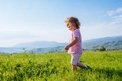 Little girl runs through a beautiful meadow stock image