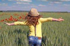 Little girl runs through a field Stock Photo