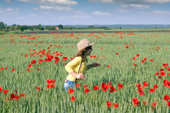 Little girl runs through a field of green wheat Stock Image