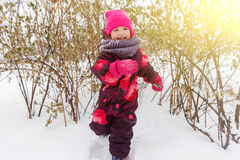 Little girl runs among forest. Trees in winter Royalty Free Stock Image
