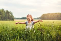 Little girl runs through a green meadow. Little cute girl runs through a green meadow stock image
