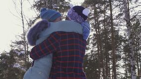 Little girl runs into his father`s arms, a sunny day. Winter forest stock video