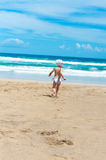 Little girl runs out to sea on the sand Royalty Free Stock Photography