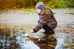 Little girl runs a paper boat in the autumn park. Stock Images