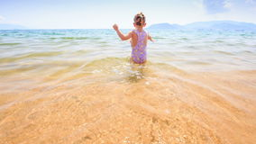 Little Girl Runs in Shallow Water to Mother in Azure Sea. Backside little girl with pigtail runs in transparent shallow water to mother dandling daughter in stock footage