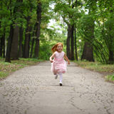 little girl runs in a summer park Stock Photo