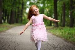 little girl runs in a summer park Stock Photos