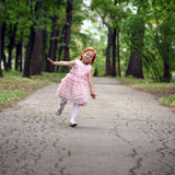 little girl runs in a summer park Stock Images