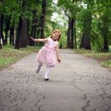 Little girl runs in a summer park. Happy little girl runs in a summer park Stock Images