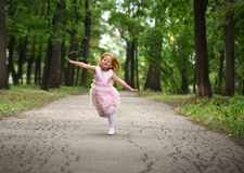 Little girl runs in a summer park Royalty Free Stock Image