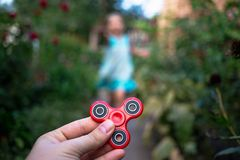 A little girl runs to hand with a fidget spinner Stock Photo
