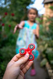 A little girl runs to hand with a fidget spinner. A little girl runs to hand with a red fidget spinner Royalty Free Stock Photography