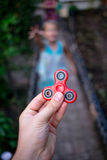 A little girl runs to hand with a fidget spinner. A little girl runs to hand with a red fidget spinner Royalty Free Stock Image