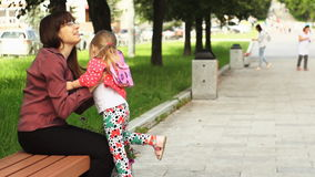 A little girl runs to her mother sitting on a bench. stock video