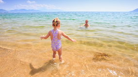 Little Girl Runs to Mother in Shallow Azure Sea Water. Backside little girl with pigtail runs in transparent shallow water to mother hugging daughter in azure stock video footage
