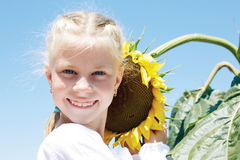 Little girl in a rustic dress with a sunflower Stock Photos