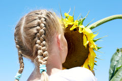 Little girl in a rustic dress with a sunflower Royalty Free Stock Photos
