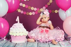 The little girl`s birthday girl was smeared into a cake. The first cake. The use of the first cake. Smash cake. stock photos