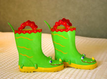 Little girl's boots. Little girl's comical boots, bright green with red handles, blue eyes, and yellow nose stock photos