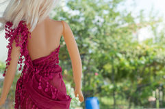 Little girl`s doll with blurry trees on background Stock Image